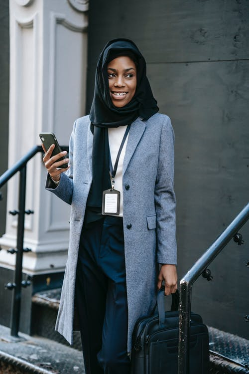 Positive young African American female in gray coat and hijab with bag and smartphone looking away while standing on stairs