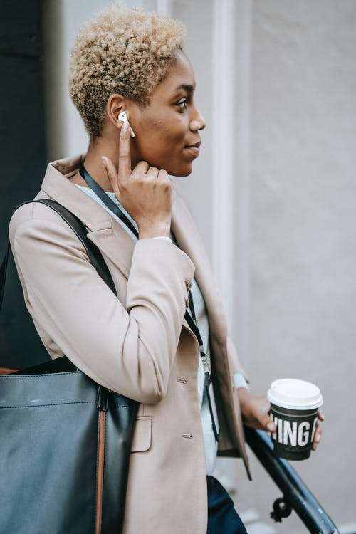 Side view of young contemplative ethnic female office worker with takeaway hot drink listening to music in wireless earphone while looking away in town