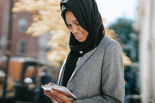 Content young African American Muslim businesswoman in stylish suit and traditional hijab smiling and reading notes on tablet while standing on city street