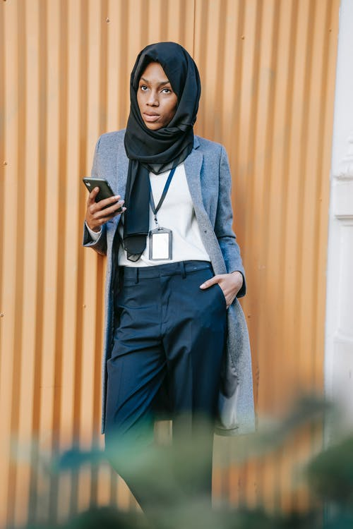 Thoughtful young black Muslim female manager in classy outfit and traditional hijab standing on city street and messaging on mobile phone