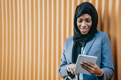 Smiling young African American female employee in traditional hijab and formal suit standing near corrugated metal wall and working on tablet