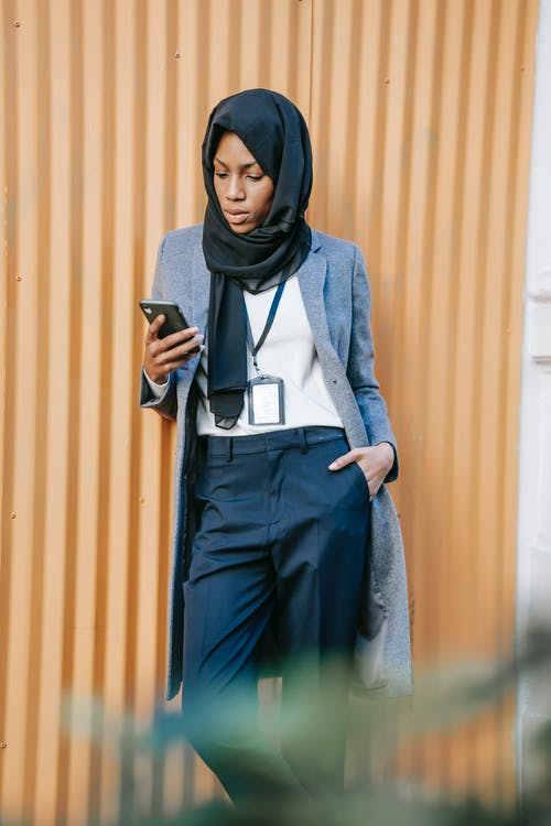 Confident young African American businesswoman reading message on smartphone on street