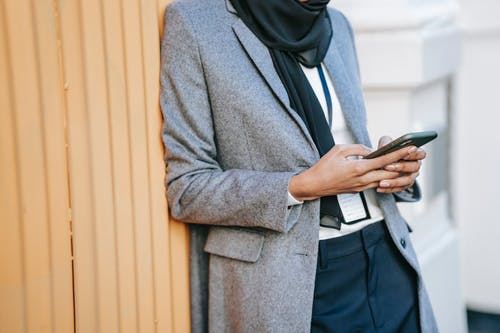 Crop stylish lady messaging on smartphone during break