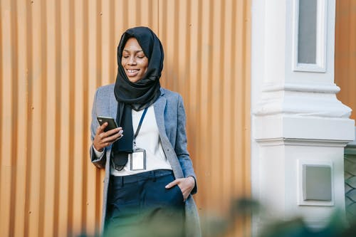 Cheerful young African American female entrepreneur in classy outfit and Islamic headscarf smiling while reading good news on smartphone and standing near building on street