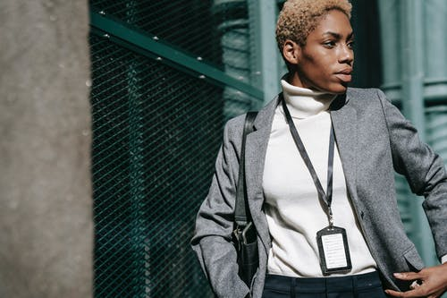 Serious young black businesswoman standing near chain link fence