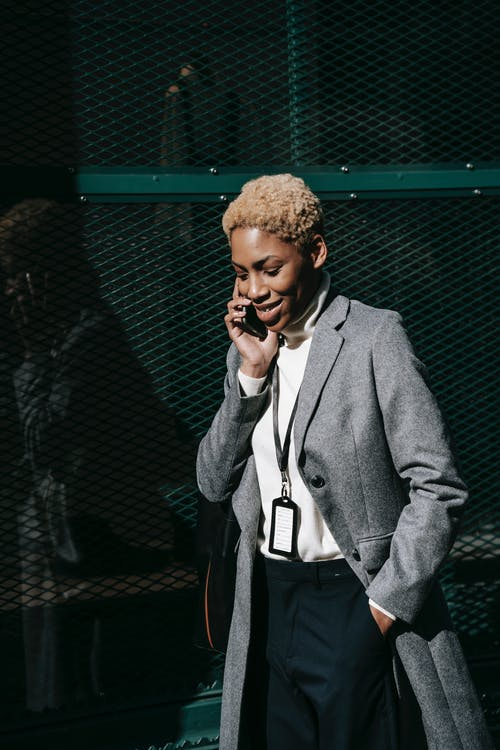 Self assured young black businesswoman with short hair and in stylish elegant outfit walking on street and smiling while having phone  conversation on sunny day