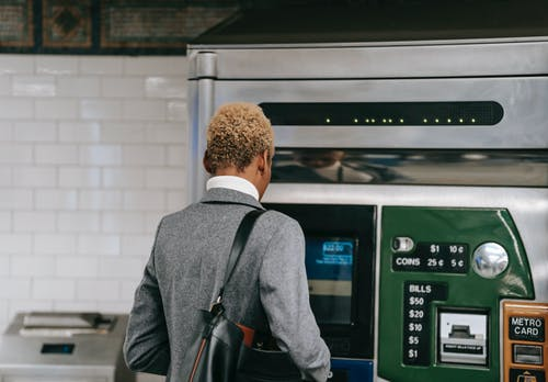 Back view of unrecognizable ethnic female manager with short dyed hair in elegant suit buying ticket with electronic machine in subway station