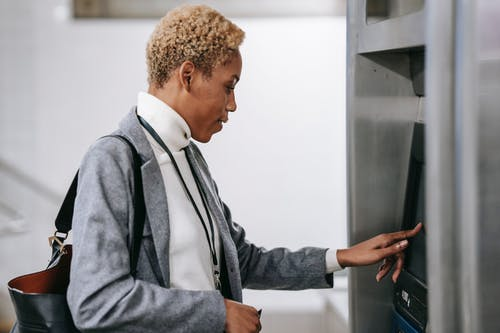 Young African American woman touching screen of ticket machine in metro station