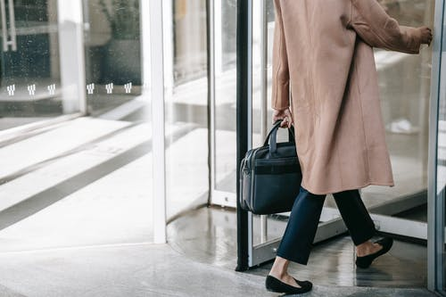 Back view of crop stylish female manager in elegant clothes with briefcase in hand entering modern building through revolving door while going to work