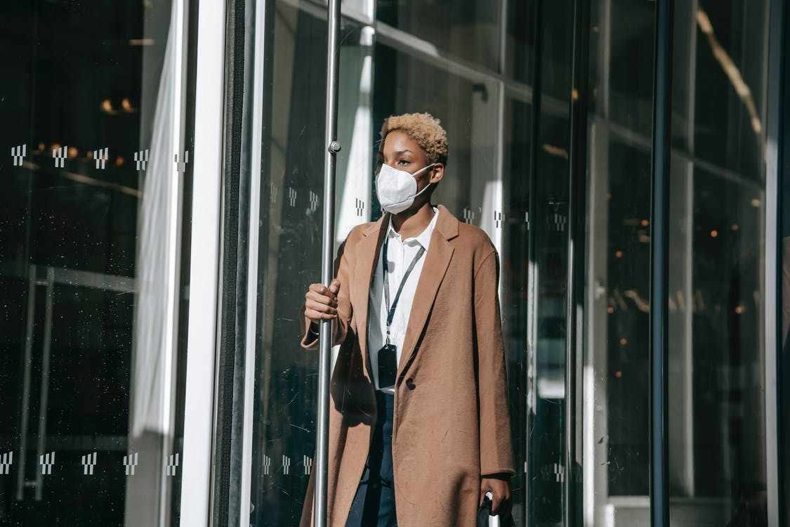 Serious young black lady in mask opening modern building door after workday