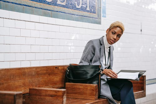 Concentrated young African American female employee with short blond hair in elegant outfit reading documents while sitting on wooden bench and waiting for train in subway station