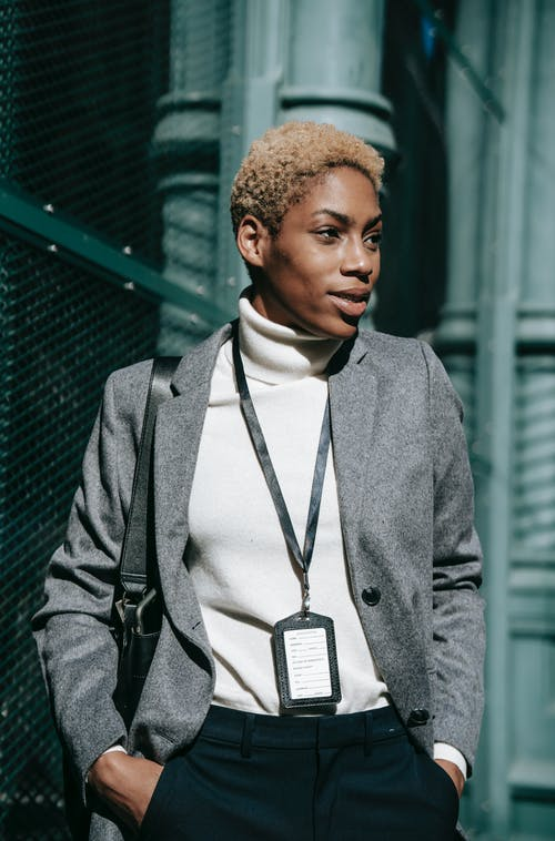 Self assured young black businesswoman standing on street with hands in pockets
