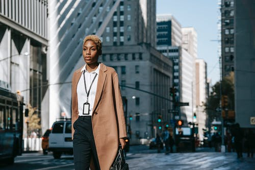 Self assured young African American female executive in stylish elegant coat and white shirt with name tag on neck walking on city street with hand in pocket