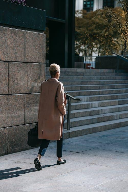 Black businesswoman walking near office building