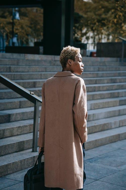 Serious black businesswoman near stairs