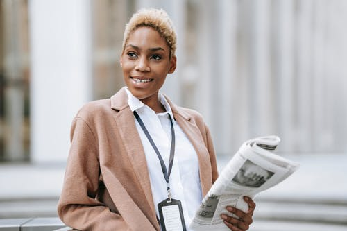 Positive young African American female entrepreneur with badge standing near stairs with newspaper leaning on railing and looking away