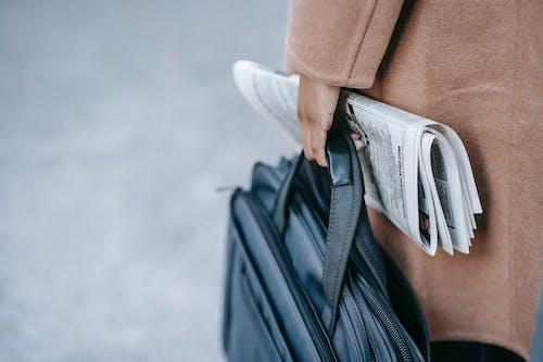 Crop anonymous female entrepreneur in elegant brown coat with laptop in bag and newspaper