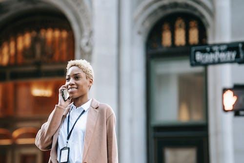 Positive black businesswoman having phone call