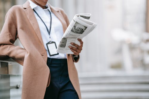 Crop unrecognizable young African American female entrepreneur in elegant brown coat with badge reading newspaper while leaning on railing near stairs