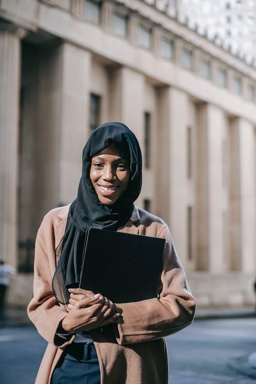 Cheerful woman with folder looking at camera