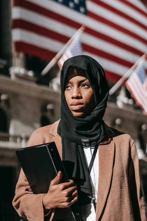 Serious young African American female student in elegant brown coat and headscarf with folder of documents for project against flags looking away