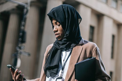 Low angle of focused young African American female in black hijab with folder with project documents chatting on smartphone