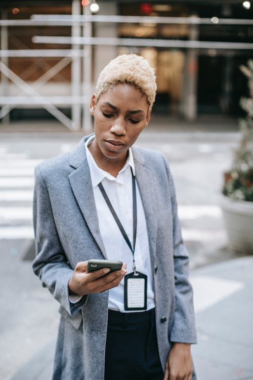 Concentrated young African American female entrepreneur in stylish gray coat with badge messaging on smartphone while standing on sidewalk near road