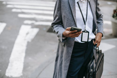 From above of crop anonymous female entrepreneur wearing stylish gray coat with badge and laptop in bag standing on sidewalk near road and messaging on smartphone