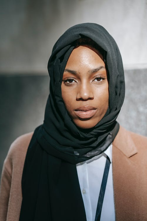 Black woman in headscarf looking at camera