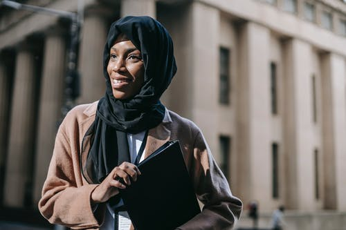 Glad young African American female student in headscarf with folder of documents looking away