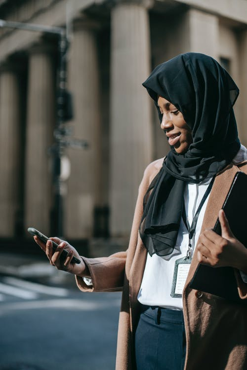 Content young African American female in black headscarf with folder of documents text messaging on phone standing near road