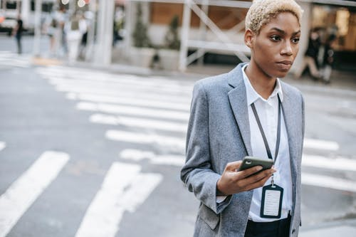 Serious black businesswoman with smartphone near road