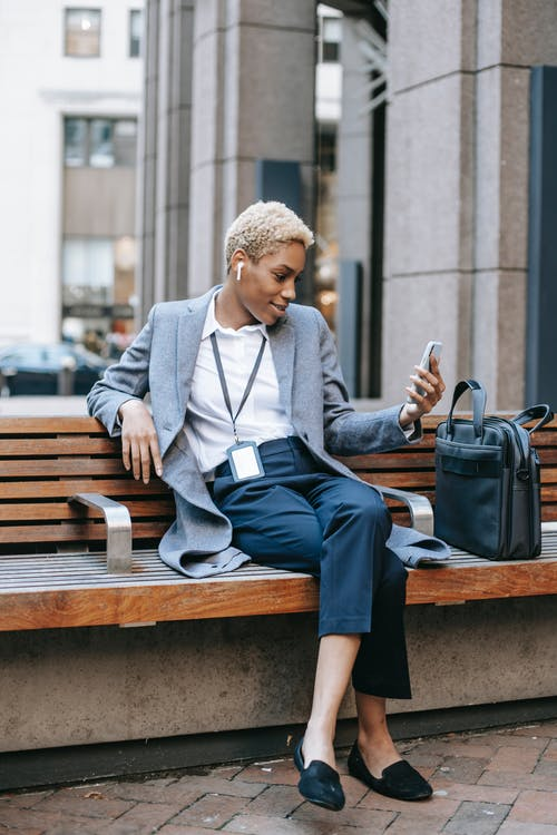 Smiling black woman having video call via smartphone while sitting outdoors