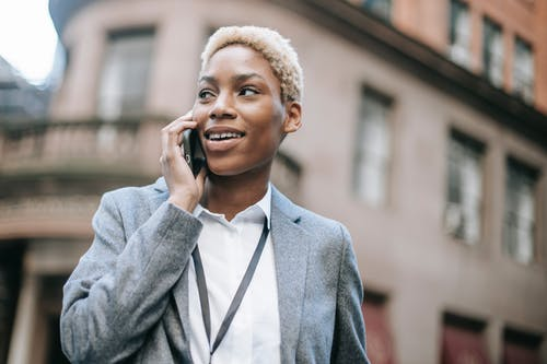 Low angle of black businesswoman wearing classy jacket speaking via modern smartphone and looking away in city street