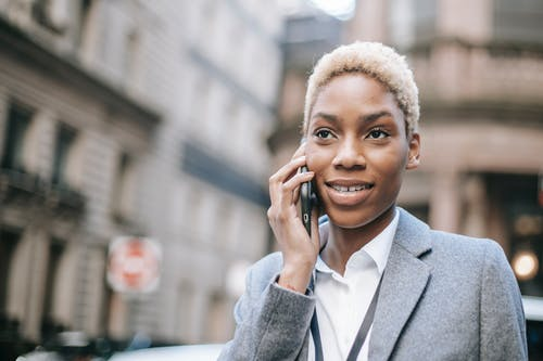 Positive black lady speaking via modern smartphone on city street