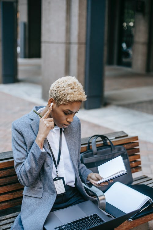 Concentrated African American female freelancer wearing formal clothes sitting with earphones on wooden bench with laptop and documents while carefully checking project details in copybook