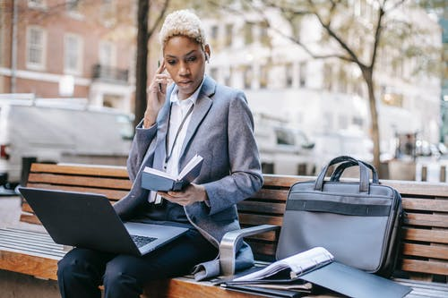 Pensive executive lady using earphones for work while sitting near city road