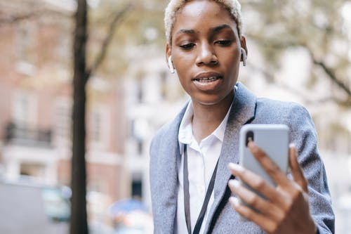 Crop serious African American lady wearing formal clothes and earphones using smartphone for video       call in city street