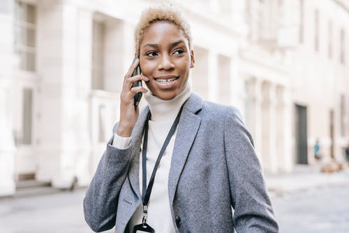Delighted African American lady wearing white turtleneck talking on mobile phone while looking away on urban background