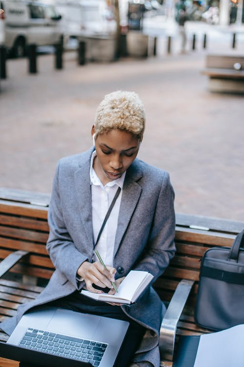 High angle of busy African American businesswoman wearing warm coat sitting with laptop on knees and taking notes in copybook