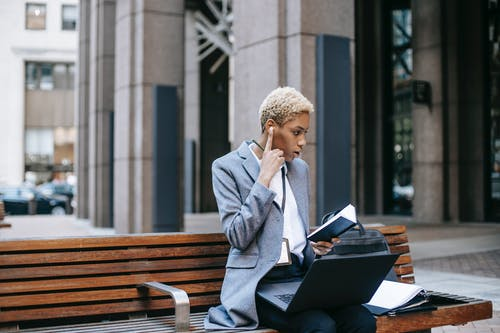Concentrated self employed female entrepreneur working remotely while sitting with laptop and papers near urban building in daytime