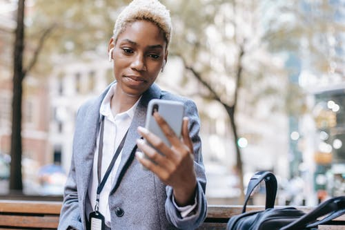 Positive young African American female wearing warm coat sitting on bench and reading text message on smartphone in daytime