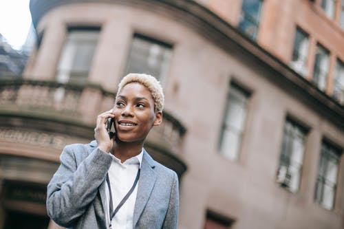 Delighted young black lady answering mobile phone on blurred background