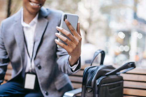 Crop unrecognizable happy young African American female employee in formal outfit and name tag smiling while having video call on mobile phone sitting on bench on city street