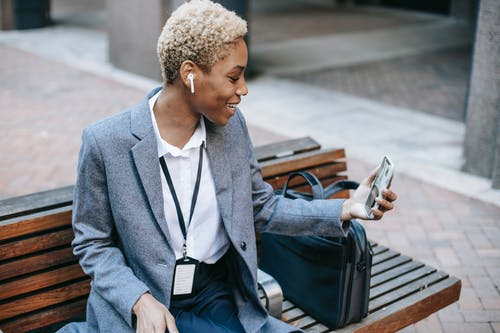 From above of positive young stylish black female entrepreneur in formal clothes and TWS earphones sitting on wooden bench on street and smiling while having video call on smartphone