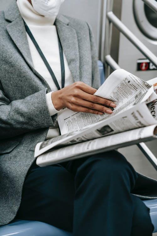 Crop anonymous black female entrepreneur in elegant outfit and medical mask reading newspaper while riding train