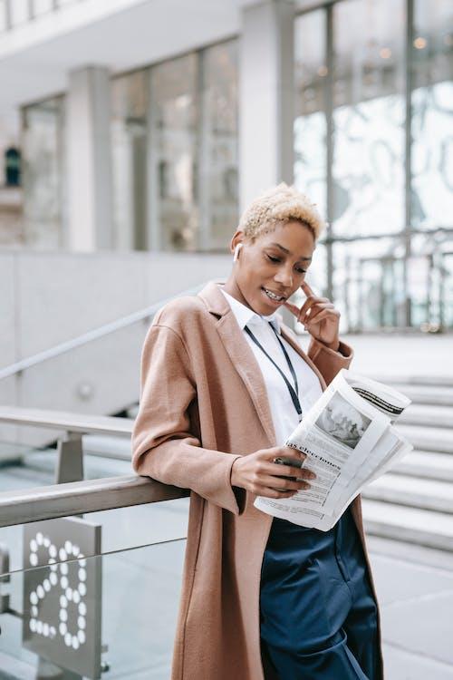 Positive young ethnic female entrepreneur reading newspaper on street