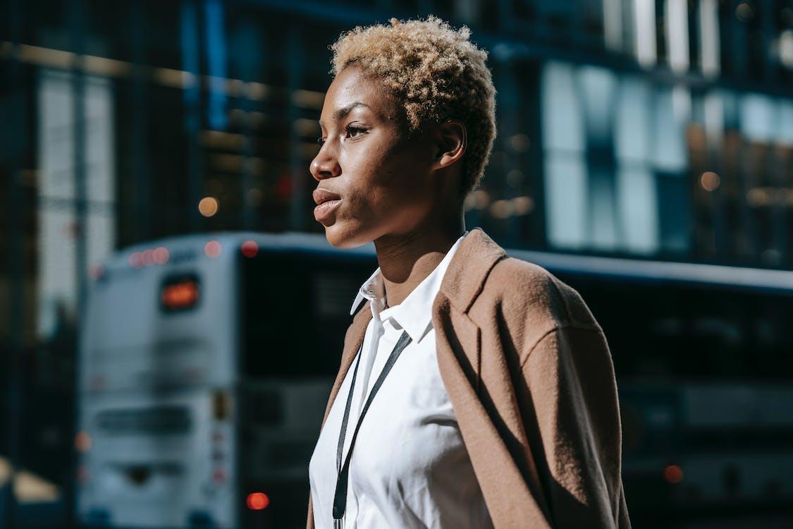 Elegant black female manager strolling on city street