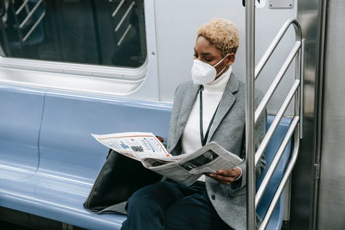 Serious black lady in medical mask reading newspaper in train