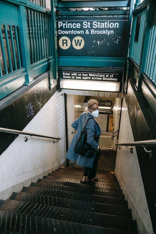 Elegant young black lady walking downstairs towards underground station